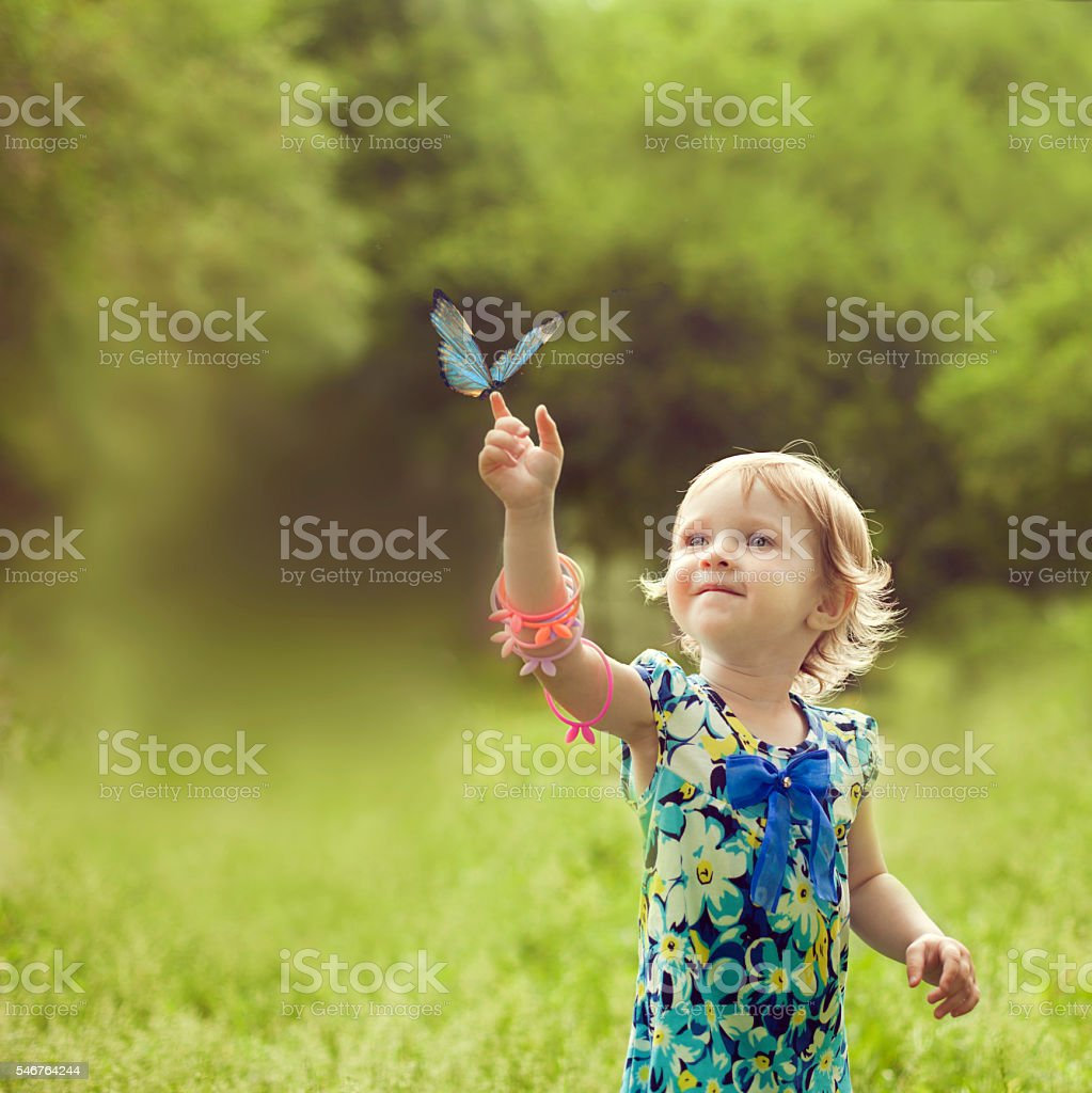 Happy girl sat on the arm of a beautiful butterfly stock photo