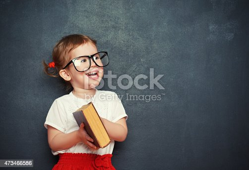 istock happy  girl schoolgirl with book from blackboard 473466586