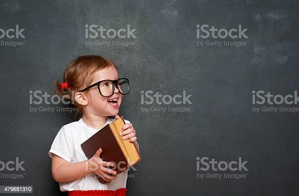 Glückliche Mädchen Im Schulmädchen Mit Buch Von Blackboard Stockfoto und mehr Bilder von Schreibtafel