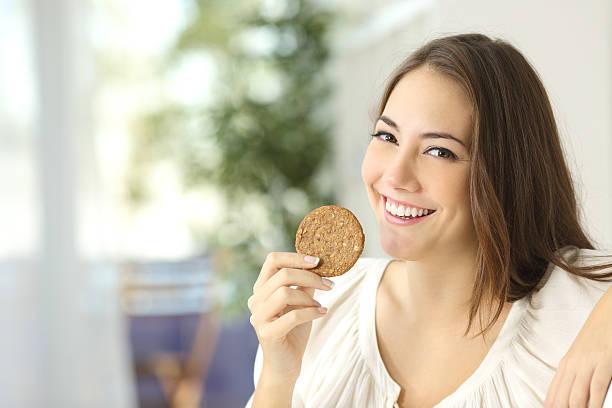 glückliche mädchen mit einem diätetik keks - zuckerfreie lebensmittel stock-fotos und bilder