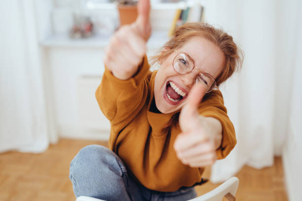 Happy girl showing thumbs up gestures stock photo