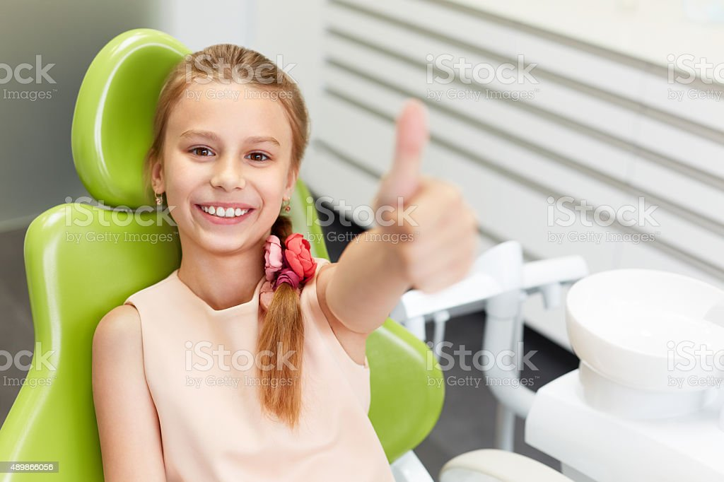 Glückliche Mädchen zeigt Daumen hoch Geste in dental clinic – Foto