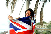 Happy girl sitting on balcony with sea view and holding British flag