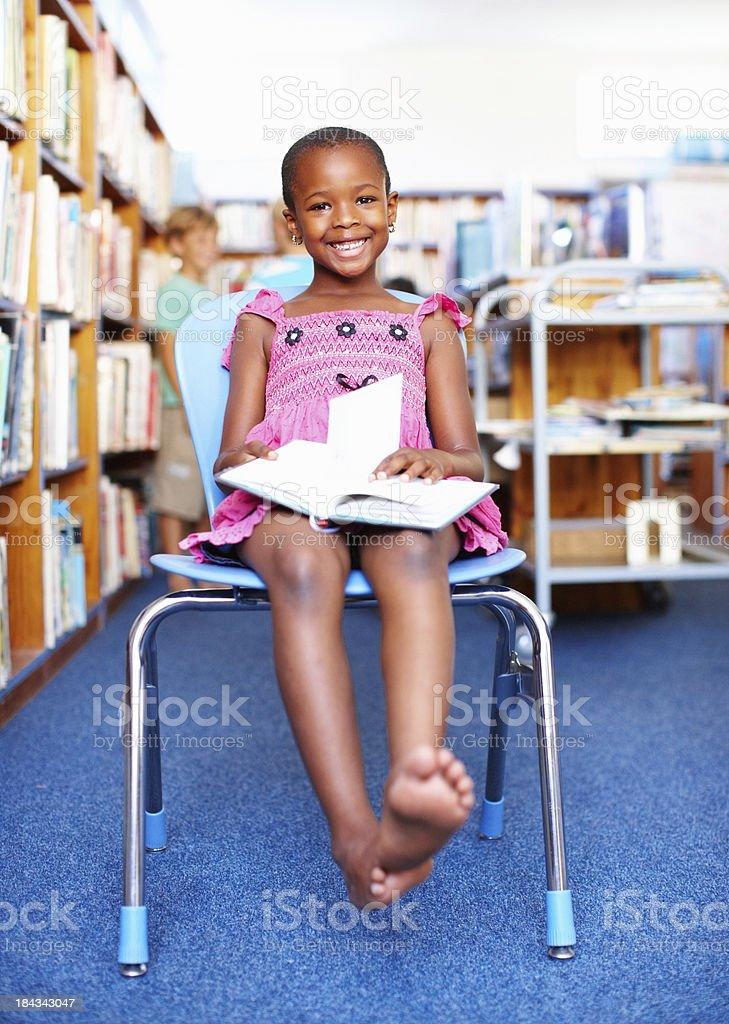 Fröhliche Mädchen sitzt auf einem Stuhl und hält ein Buch – Foto