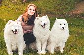 istock Happy girl sitting with white Samoyed dogs 1048690532