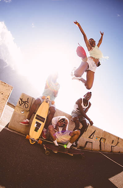 Happy girl skater jumping over friends with joy stock photo