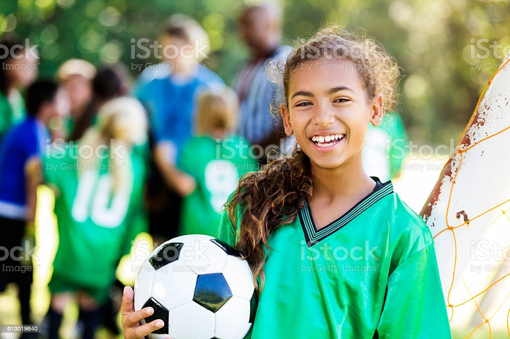 Happy girl smiles after winning soccer game stock photo