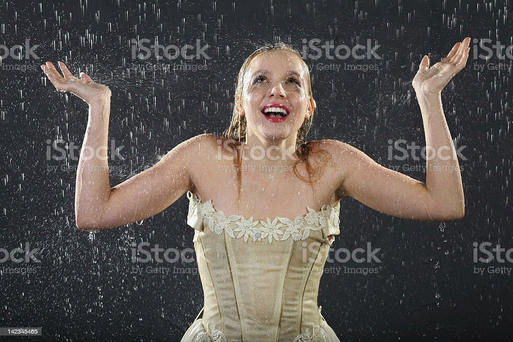 Happy girl smiles in rain and catches drops by hands stock photo