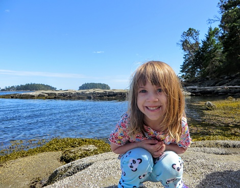 A happy girl smiling for the camera as she explores the coast of the gulf islands in British Columbia, Canada.