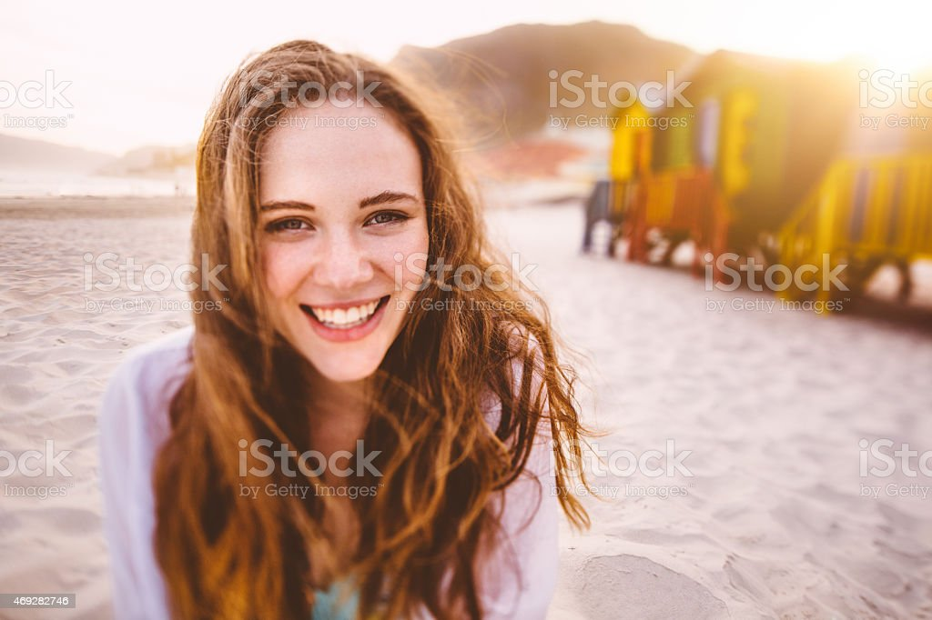 Happy girl smiling in front of colourful beach huts stock photo
