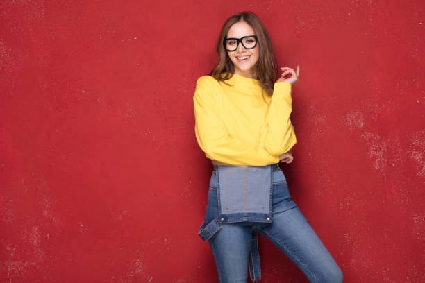 glückliches mädchen lächelt, steht auf rotem grund. - damen jeans sale stock-fotos und bilder