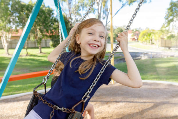 Happy Girl Smiling While Playing On Swings At The Park stock photo
