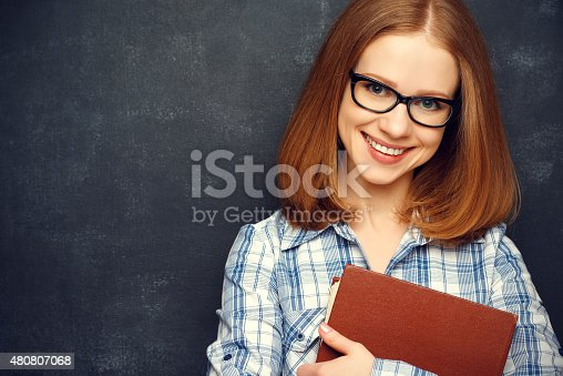 639569206 istock photo happy girl student with glasses and book from blackboard 480807068