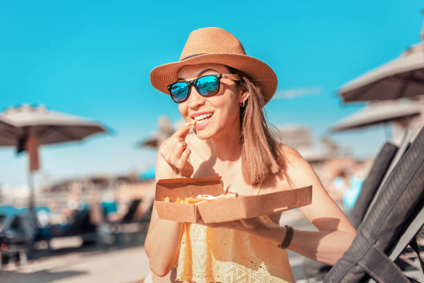 Happy girl sunbathing on the beach and snacking with fast food french fries stock photo