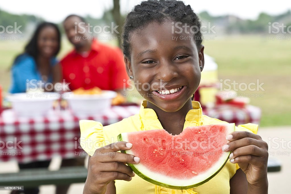 Happy Girl Taken Bite Out of Watermelon at Family Picnic stock photo
