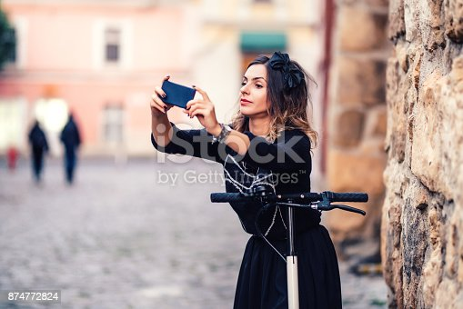 874772840istockphoto Happy girl taking selfie with camera while riding a kick scooter 874772824