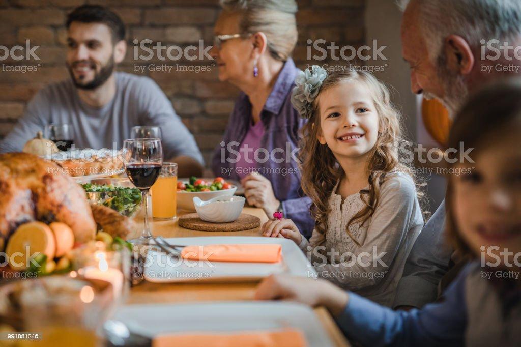 Fille heureuse de parler à son grand-père pendant le dîner à la table à manger. - Photo