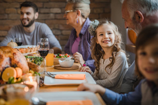 happy girl talking to her grandfather during dinner at dining table. - family dinner stock photos and pictures