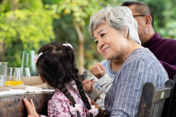 Glückliches Mädchen im Gespräch mit ihrer Großmutter am Esstisch – Foto