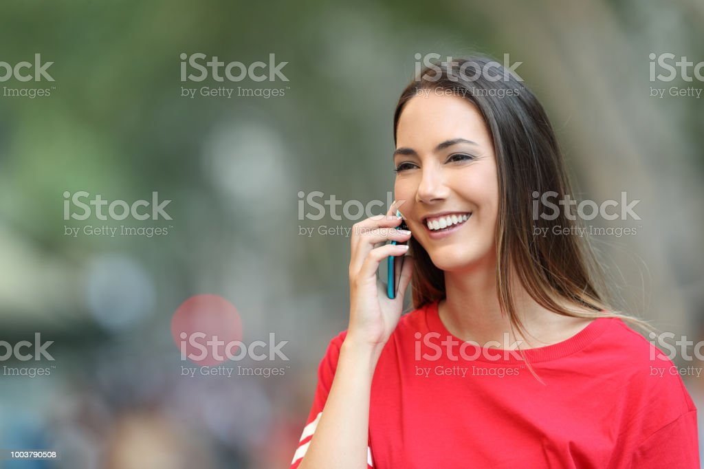Happy girl in red talks on phone and walks on the street looking away