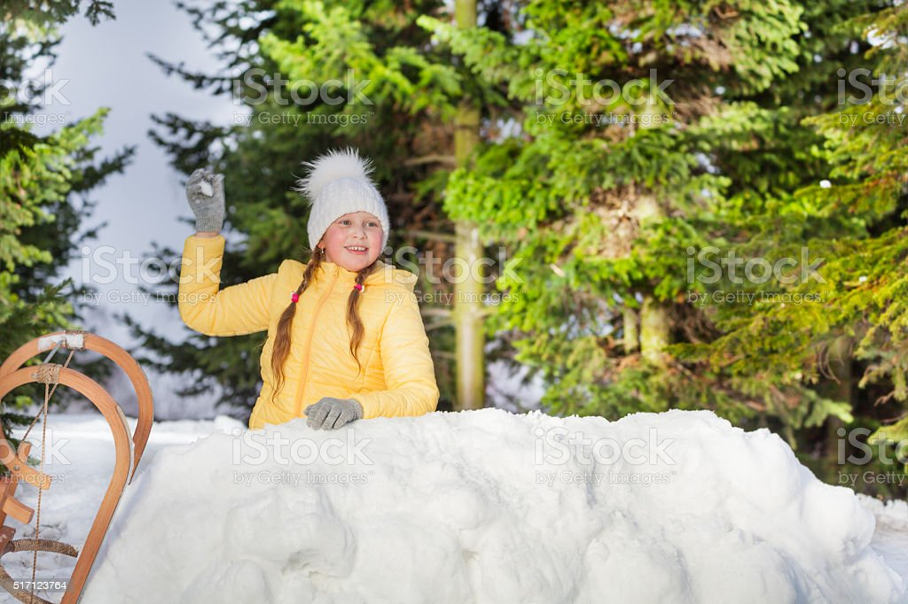 Happy girl throwing snowball from the snow tower stock photo