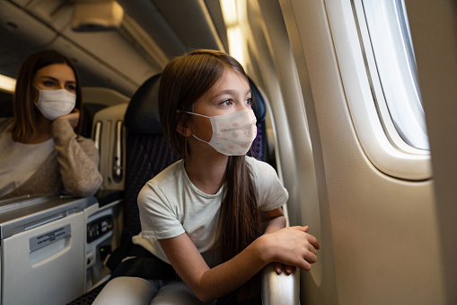 Happy girl traveling by plane wearing a facemask