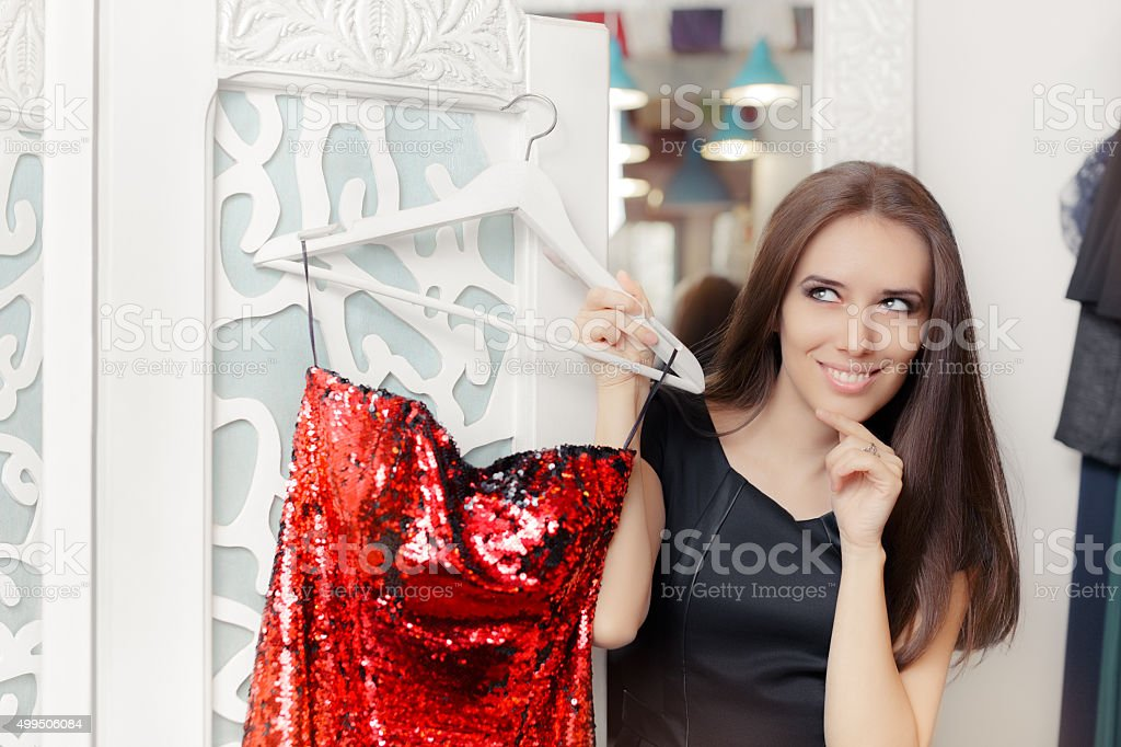 Happy Girl Trying on Red Party Dress in Dressing Room stock photo