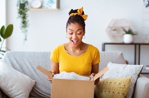 Buying Via Internet. Excited afro girl sitting on sofa unboxing cardboard delivery package, copy space