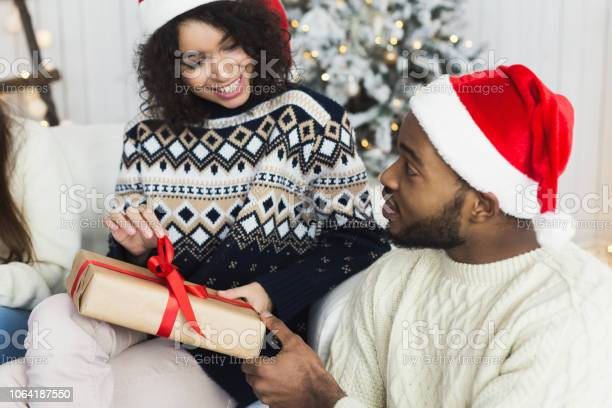 Happy Girl Unwrapping Christmas Present From Her Boyfriend Stock Photo - Download Image Now