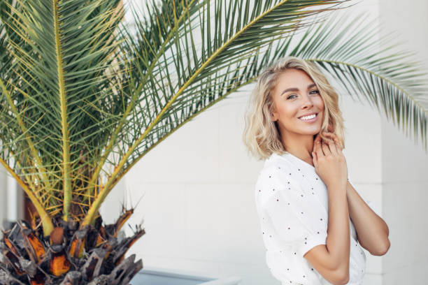 Happy girl walking near palm trees on a summer sunny day stock photo