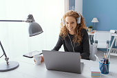 Happy young student girl wearing headphones and watching movies online, leisure and entertainment concept