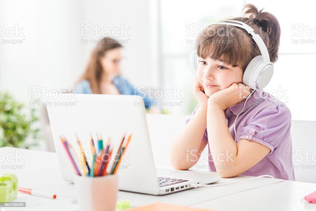 Garota feliz assistindo vídeos no seu laptop - foto de acervo