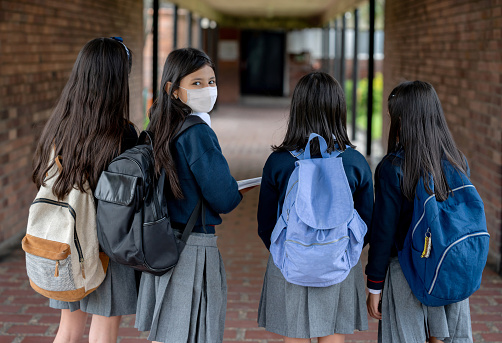 Happy girl wearing a facemask at the school while hanging around with her friends - lifestyle during the COVID-19 pandemic