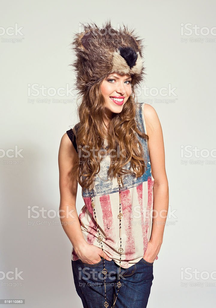 Happy Girl wearing fur hat Portrait of happy young woman wearing fur hat, smiling at the camera. Studio shot, white background. 20-24 Years Stock Photo