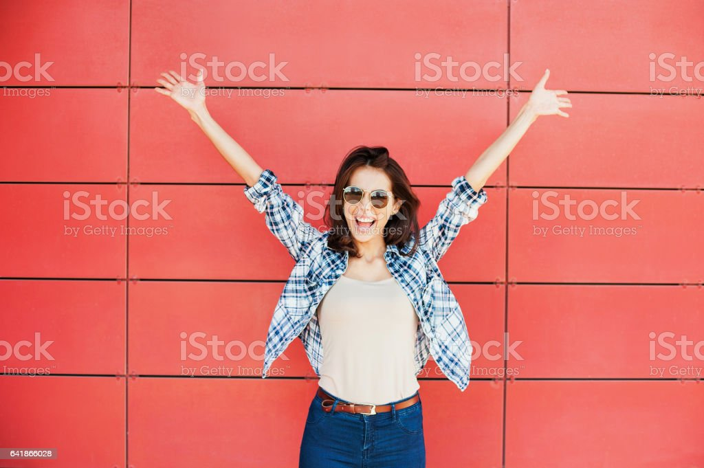 Happy girl with arms raised against red wall stock photo