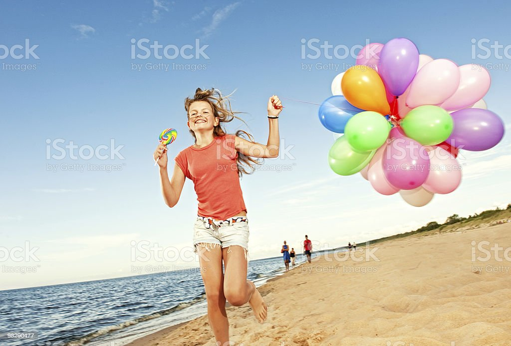Happy girl with balloons running on the beach royalty-free stock photo