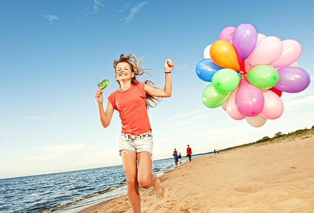 Happy girl with balloons running on the beach stock photo