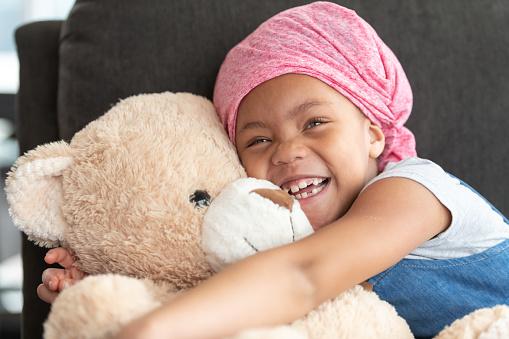 Happy girl with cancer hugs teddy bear