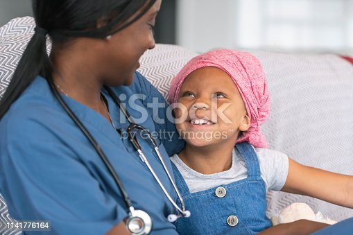 istock Happy girl with cancer sits with home caregiver 1141776164