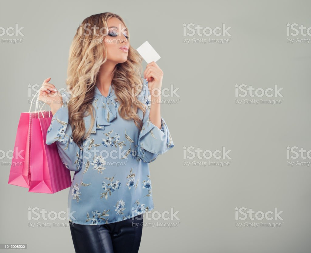 Happy girl with card and shopping bags. Woman holding credit card on...