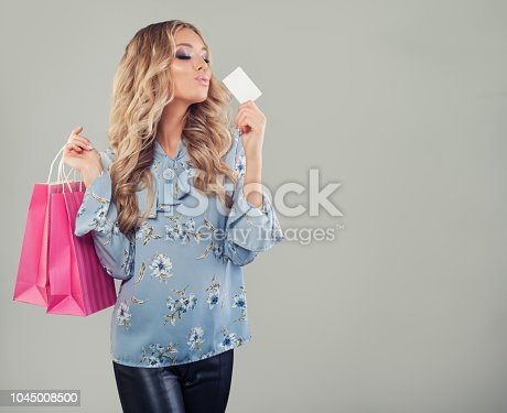 Happy girl with card and shopping bags. Woman holding credit card on banner background with copy space.
