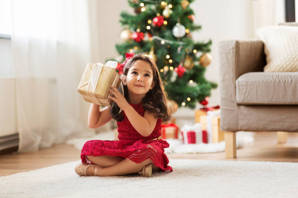 happy girl with christmas gift at home stock photo