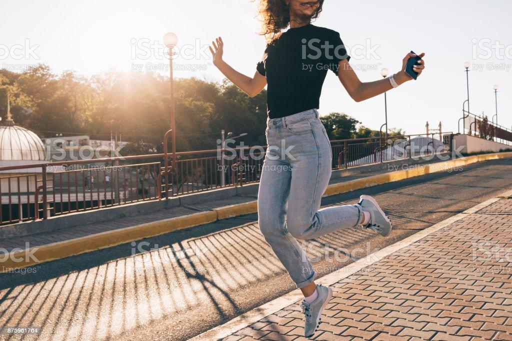 Garota feliz com cabelo castanho encaracolado, saltando na cidade - foto de acervo