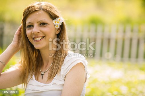 Happy girl with daises in hair enjoying spring day in nature