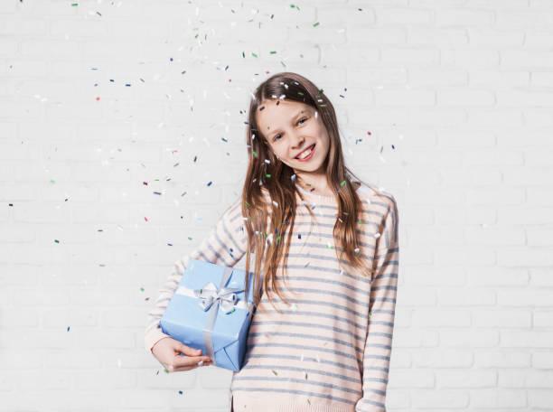 glückliches mädchen mit fallenden konfetti auf party - jugendliche geburtstag geschenke stock-fotos und bilder