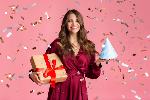 627933752 istock photo Happy girl with gift box and birthday hat under confetti rain 1208526264
