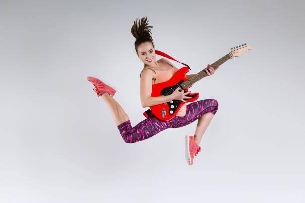 Happy girl with guitar in studio stock photo