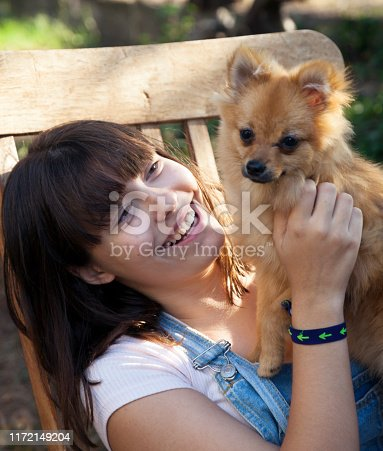 istock Happy girl with her little pomeranian 1172149204