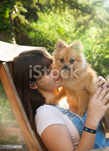 istock Happy girl with her little pomeranian 1172149205