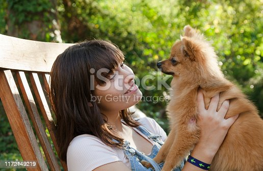 istock Happy girl with her little pomeranian 1172149219